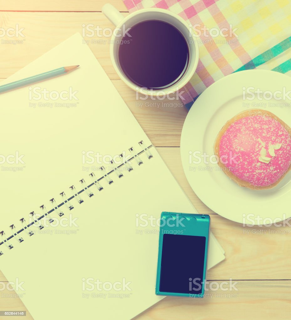 Travel blogger items on colorful cafe table with coffee and snack stock photo