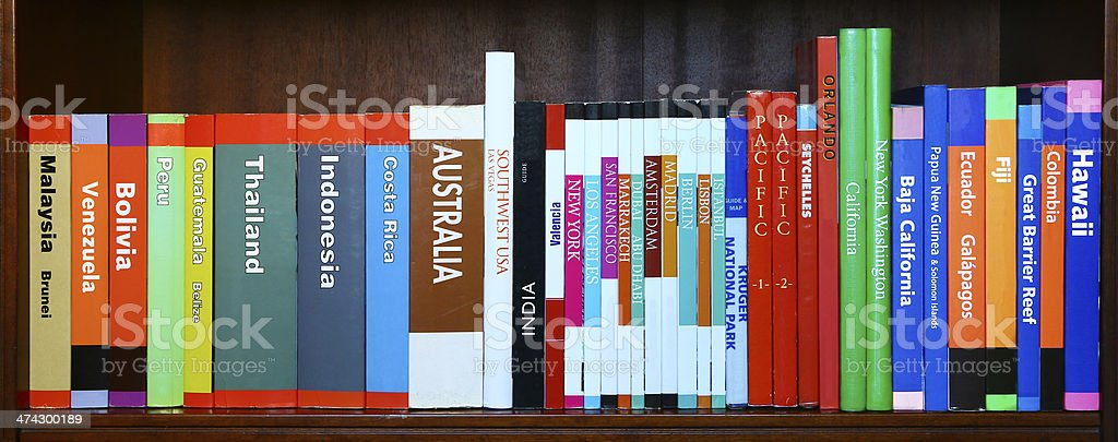 Travel books on horizontal shelf stock photo