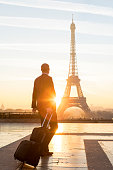 Travel businessman walking with suitcase at Eiffel Tower in Paris