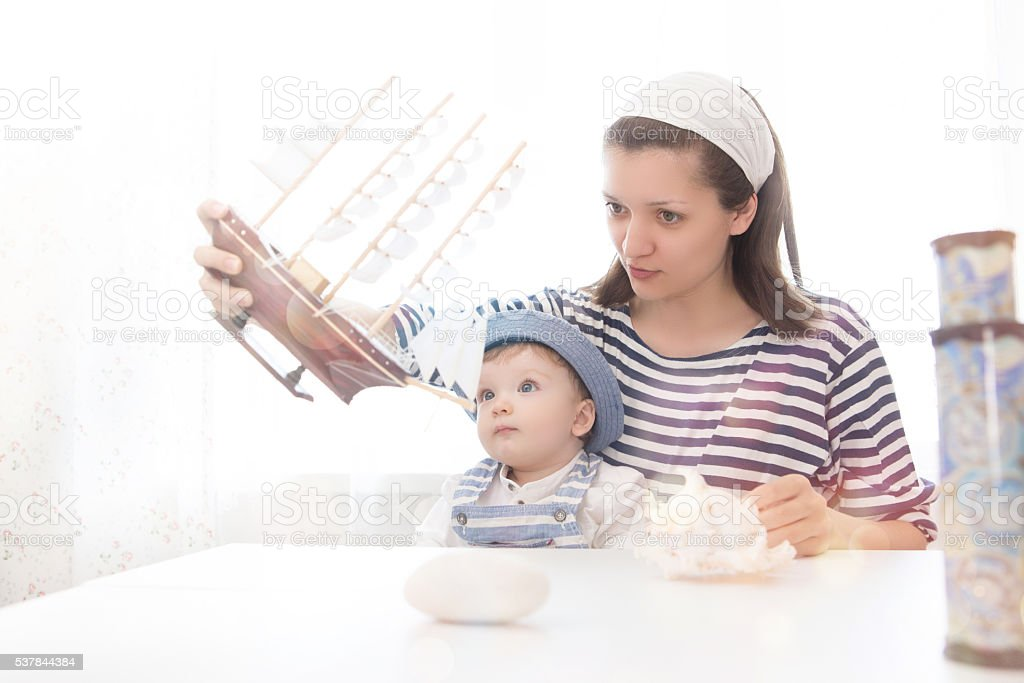 Travel concept. Mother and son playing with the ship. stock photo