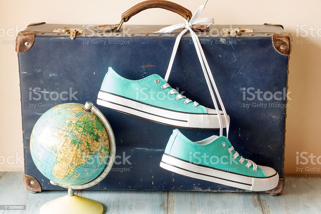Travel concept with holiday suitcase, shoes and globe stock photo