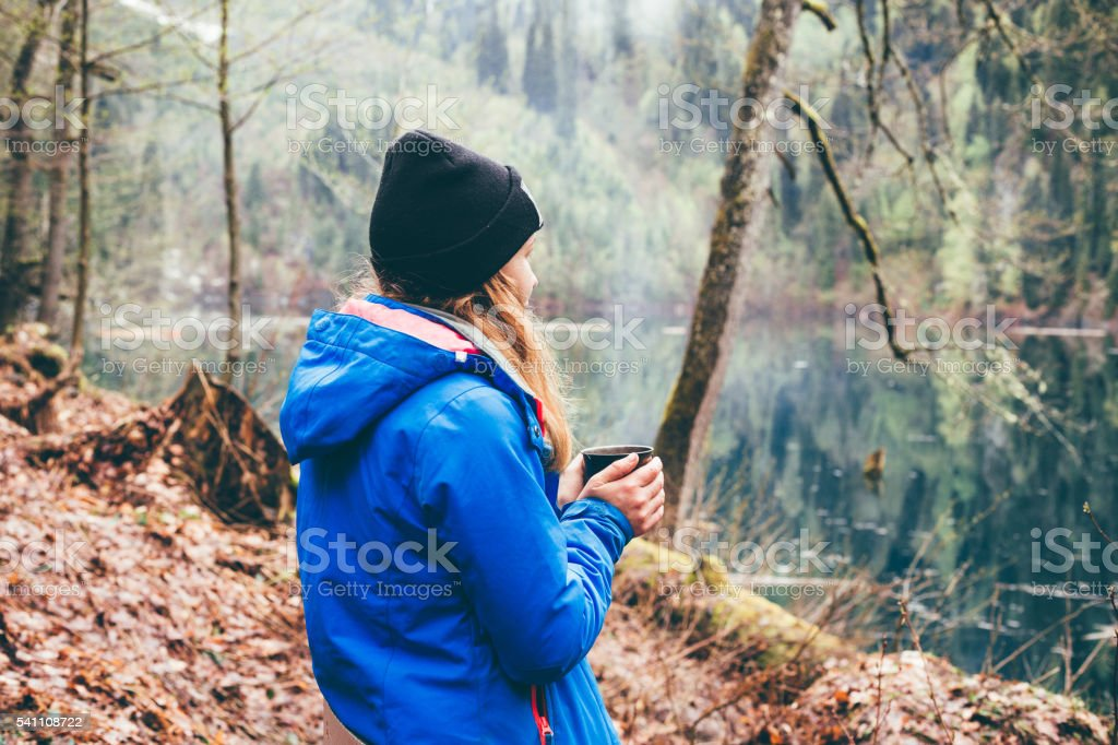 Travel girl drinking from a mug in the outdoor. stock photo