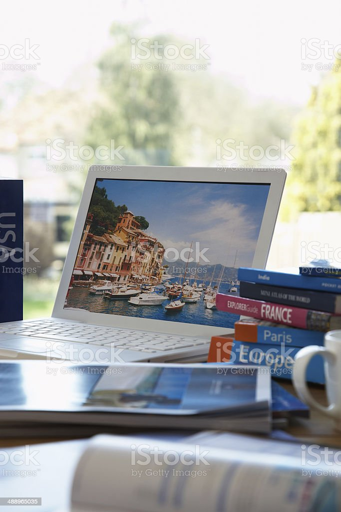 Travel guides next to laptop on table stock photo