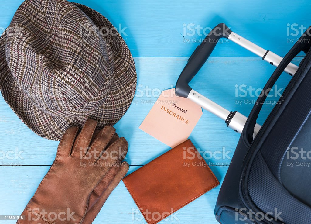 Travel insurance concept. Suitcase, hat, gloves, passport case, insurance tag. stock photo