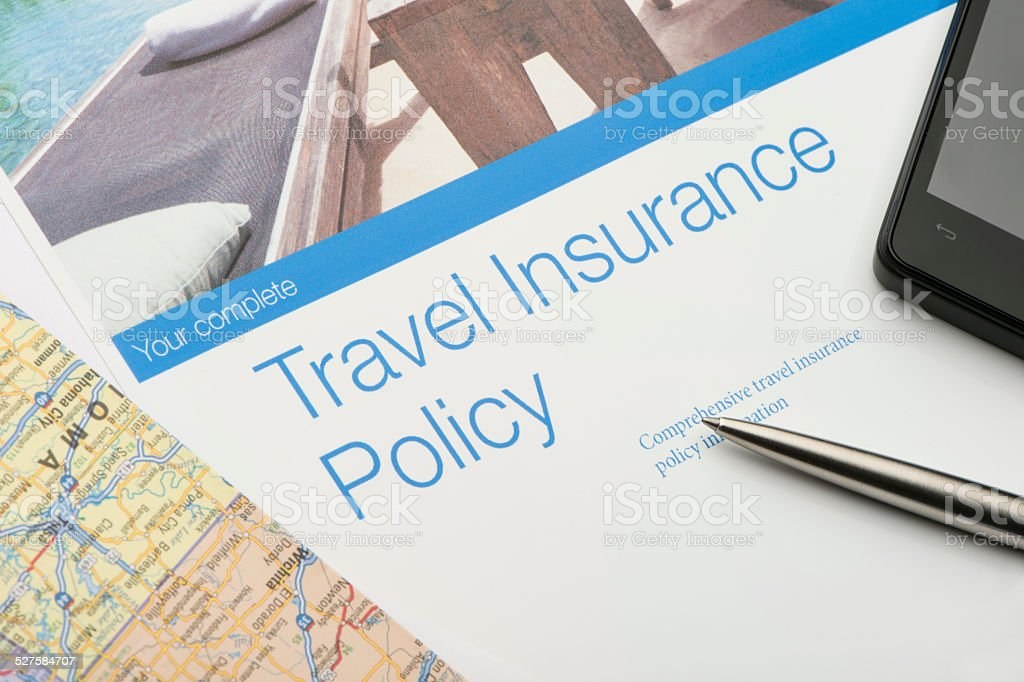 Travel insurance policy document with paperwork and technology. There...