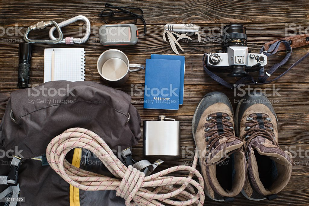 Travel items near backpack on the floor for mountain trip stock photo