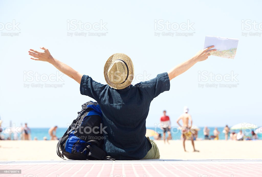 Travel man sitting by beach with arms outstretched stock photo