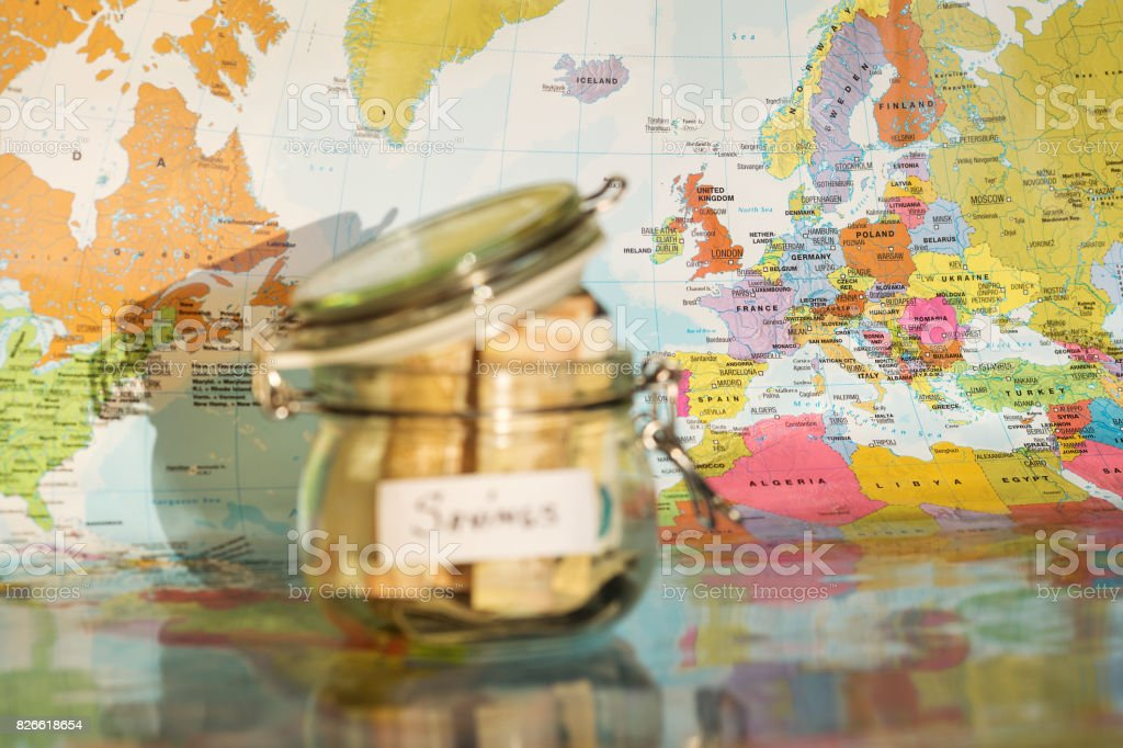 Travel money savings in a glass jar with map in background stock photo