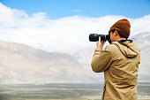travel photographer journalist holding a dslr camera in mountain