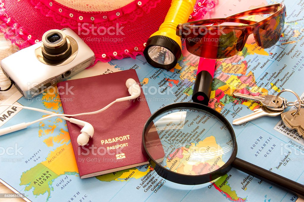 Travel planning over world map. Passport and magnifying glass stock photo