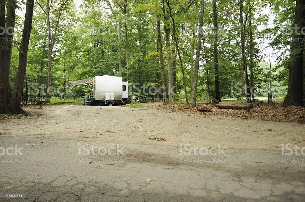 Travel trailer in campground royalty-free stock photo