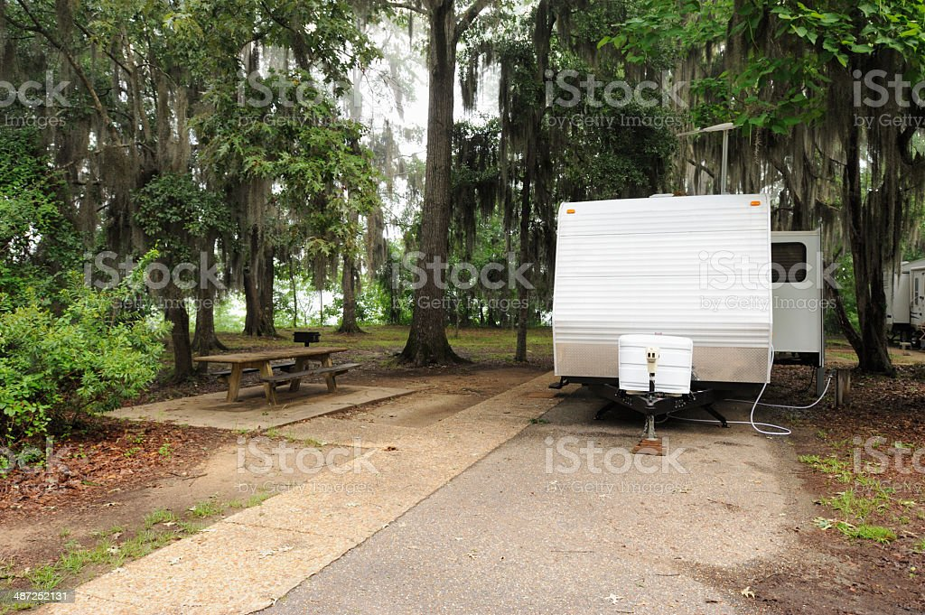RV travel trailer in wooded campsite royalty-free stock photo