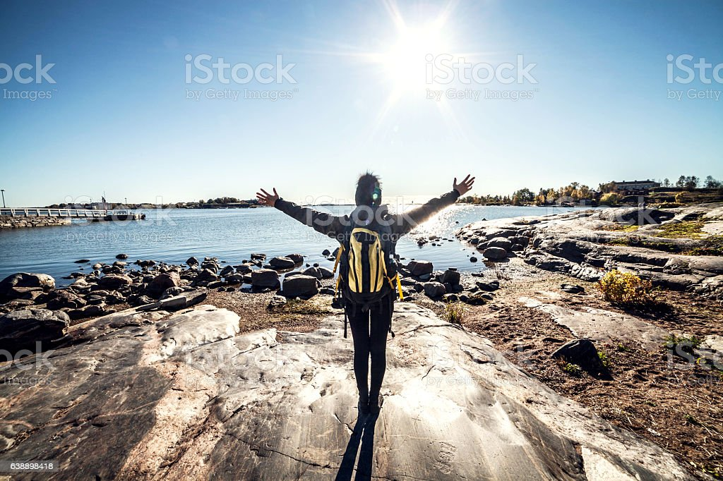 Travel woman arms outstretched by the sea stock photo