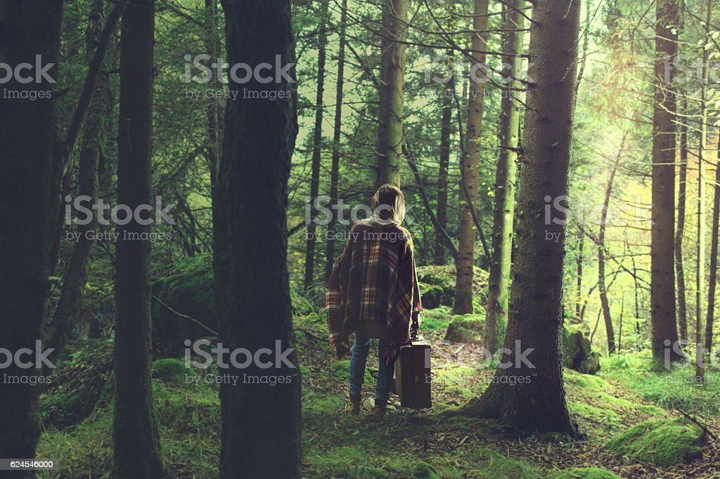 travel woman seeks way out of a mysterious forest stock photo