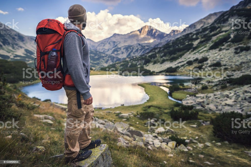 Traveler hiking in mountains and enjoying a view from above stock photo