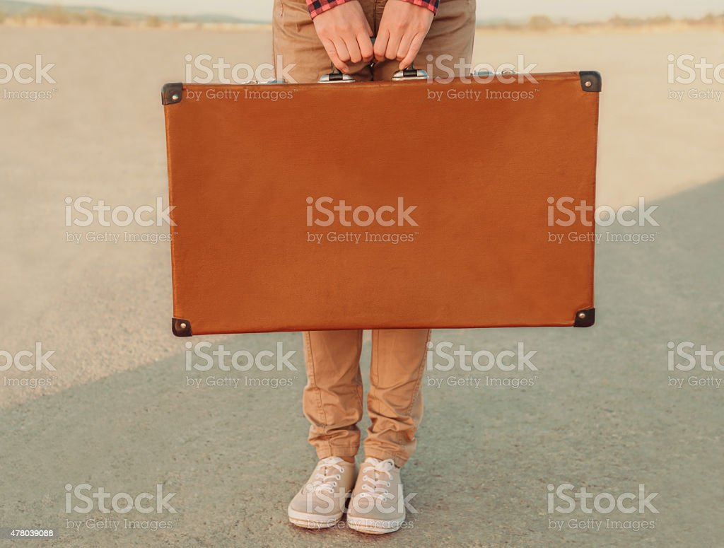 Traveler holding a suitcase, view of hands stock photo