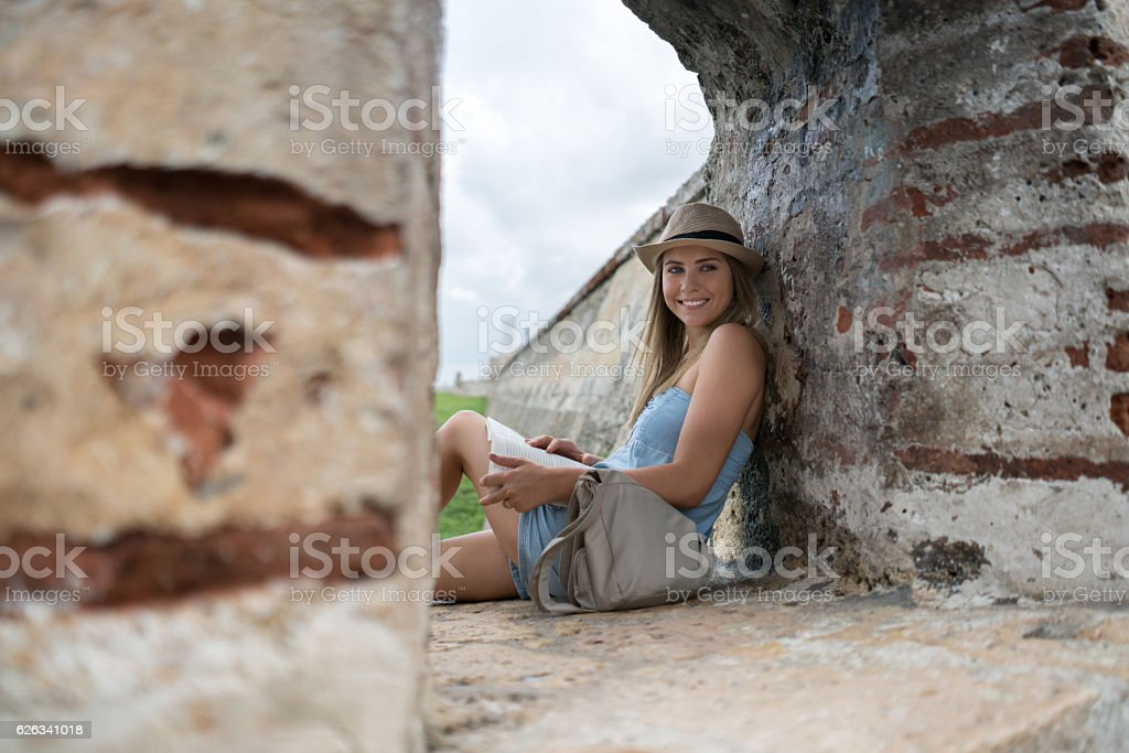 Traveler in Cartagena reading a book in the wall stock photo