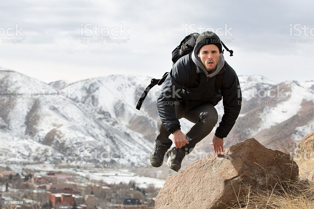 Traveler jumping over a rock stock photo