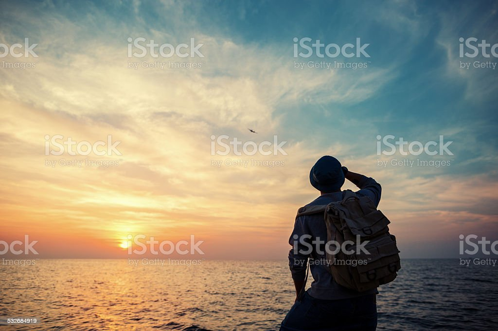 traveler looking at airplane at sunset stock photo