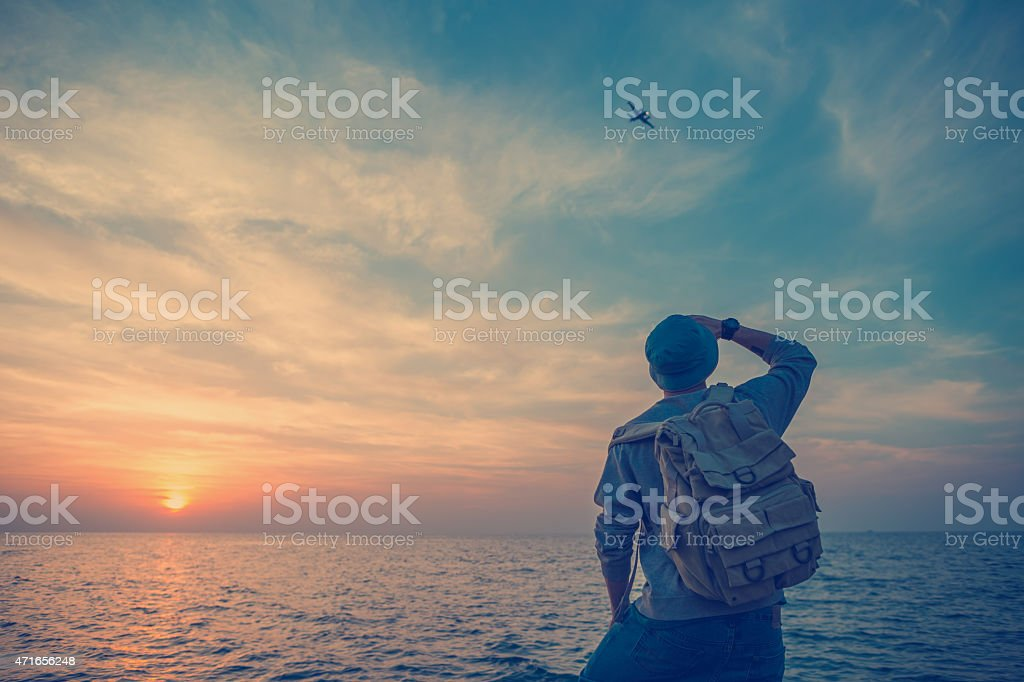 traveler looking at airplane at sunsetin the sky stock photo