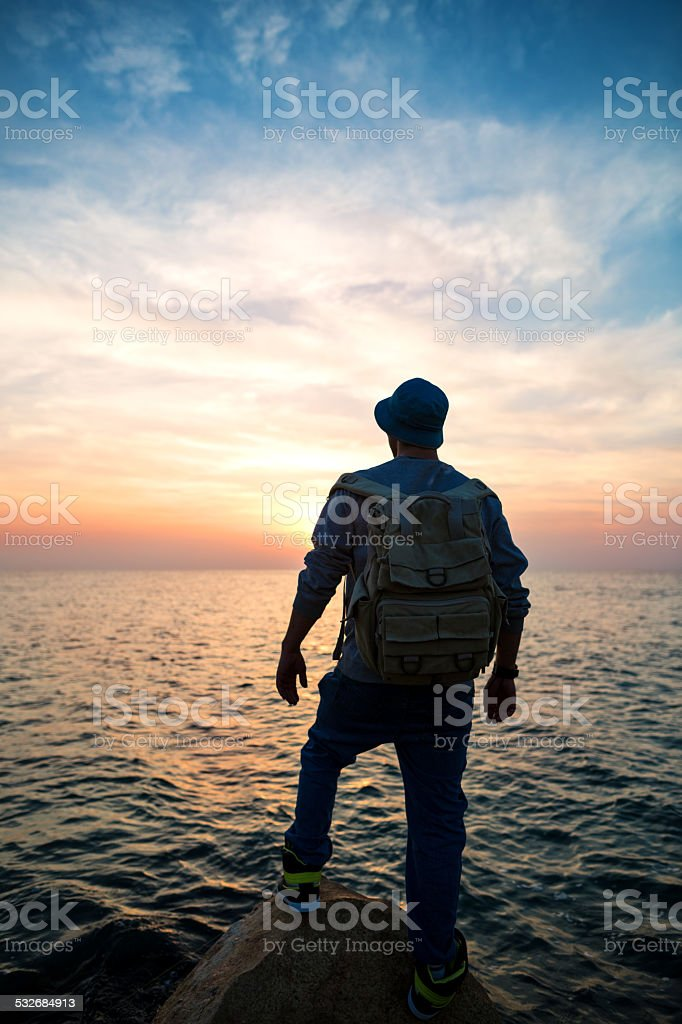 traveler looking at sunset stock photo