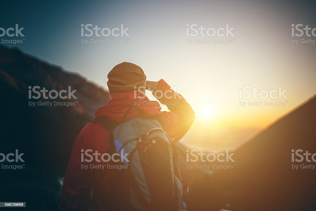Traveler looking the sunrise on top of the mountain stock photo