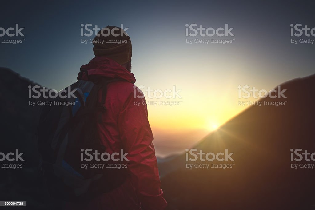 Traveler looks at the setting sun in the mountains stock photo