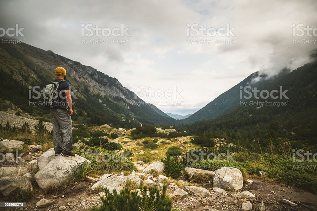 Traveler looks on valley in mountains stock photo