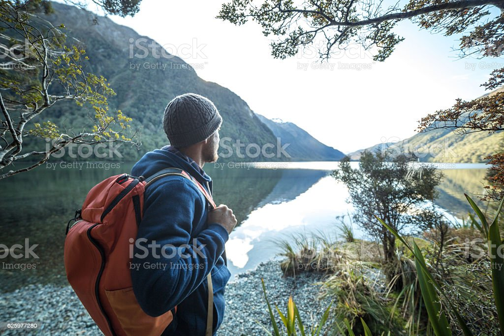 Traveler man by the mountain lake contemplates beautiful landscape stock photo