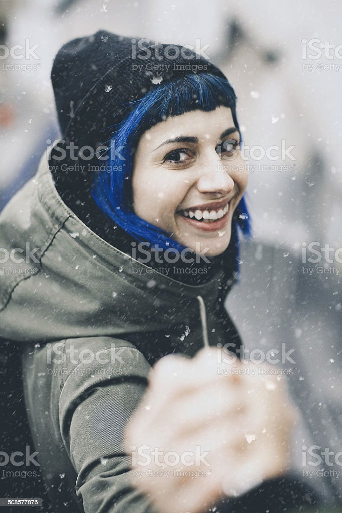 Traveler man follows a woman under the snow stock photo