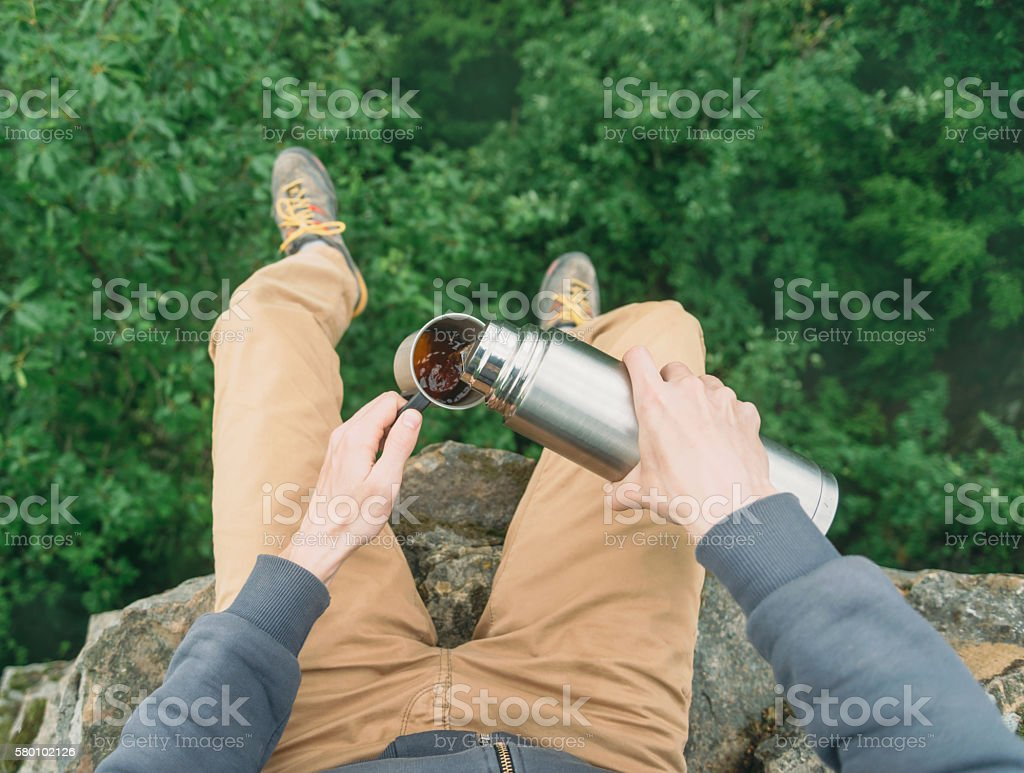 POV of traveler pouring tea from thermos stock photo