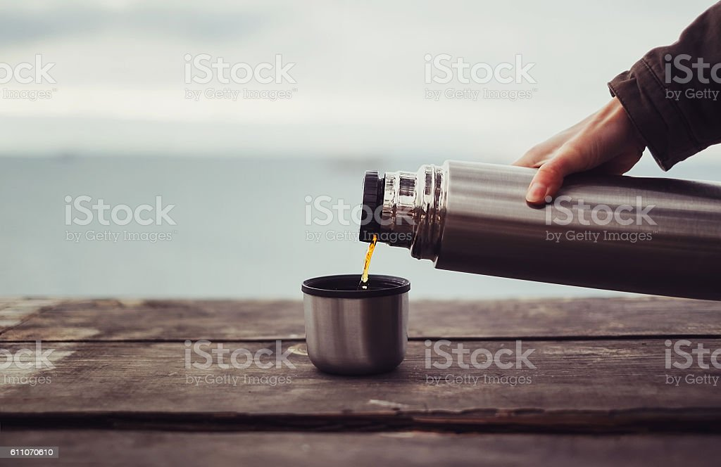 Traveler pouring tea from thermos stock photo