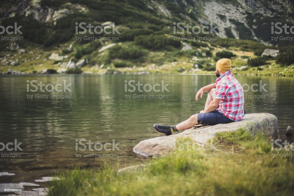 Traveler relaxing at the lake in mountains stock photo
