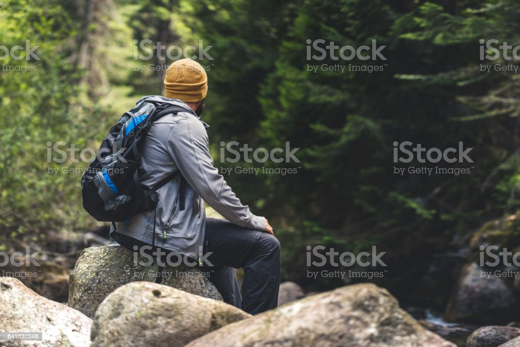 Traveler resting sitting on a rock in the forest stock photo