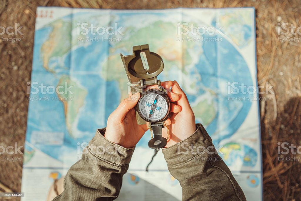 Traveler searching direction with a compass on background of map stock photo