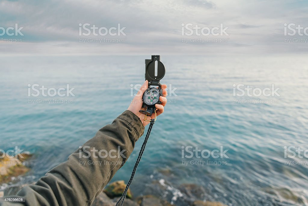 Traveler searching direction with a compass stock photo