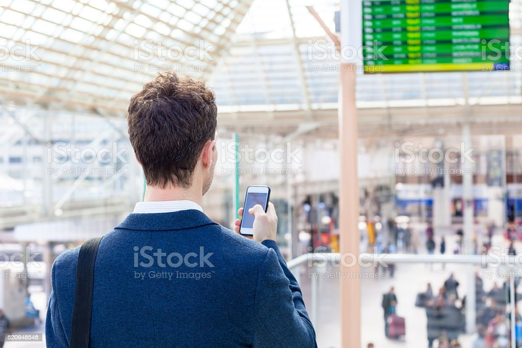 Traveler sending text message on smartphone in train station stock photo