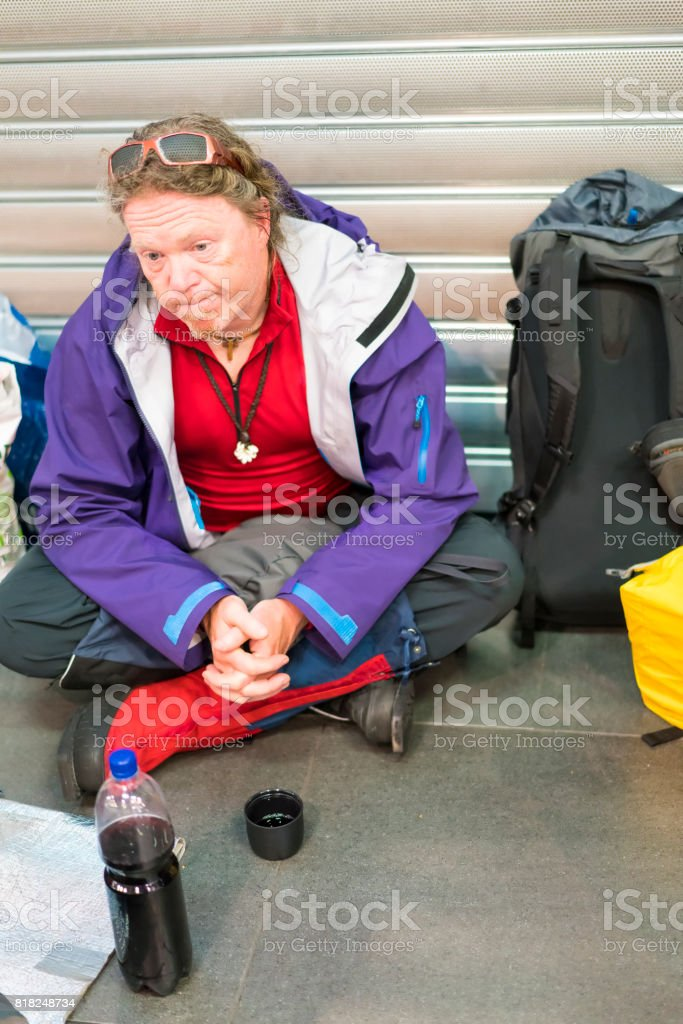 Traveler siting on the floor at night on airport stock photo