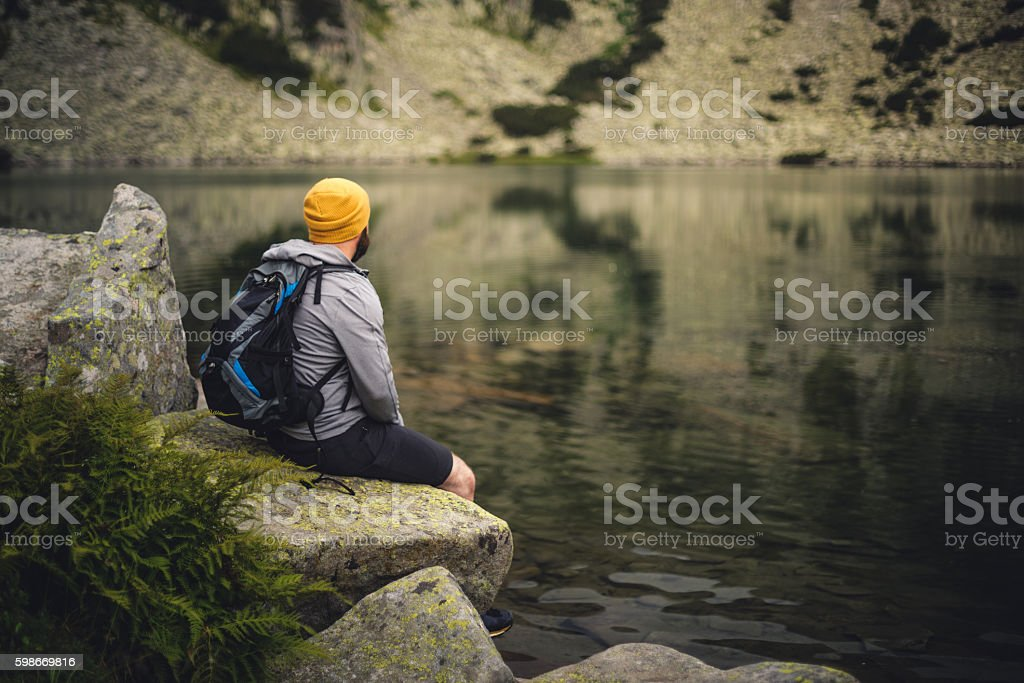 Traveler sits on a rock at lake in mountains stock photo