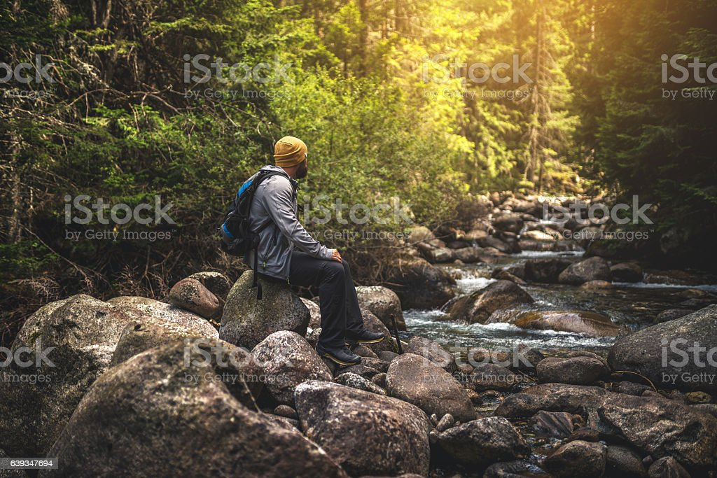 Traveler sits on a rocks at the stream in mountains stock photo