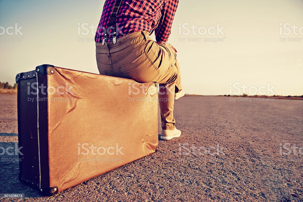 Traveler sits on suitcase stock photo