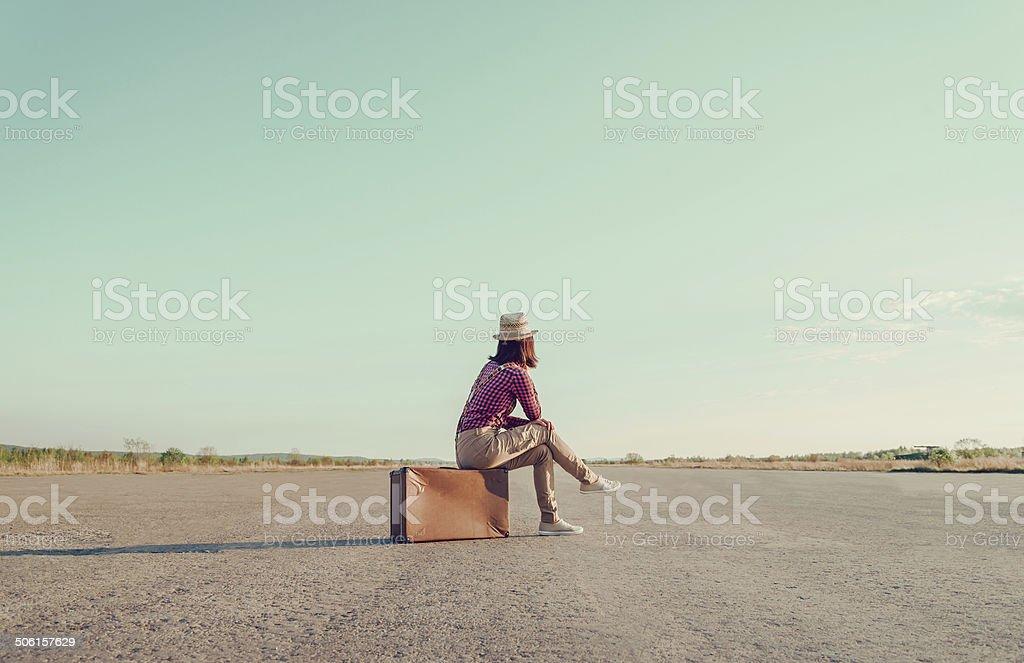 Traveler sits on vintage suitcase stock photo