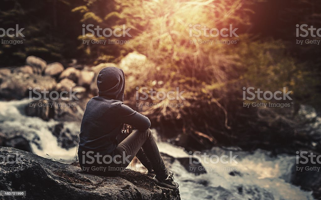 Traveler sitting in the forest near river stock photo