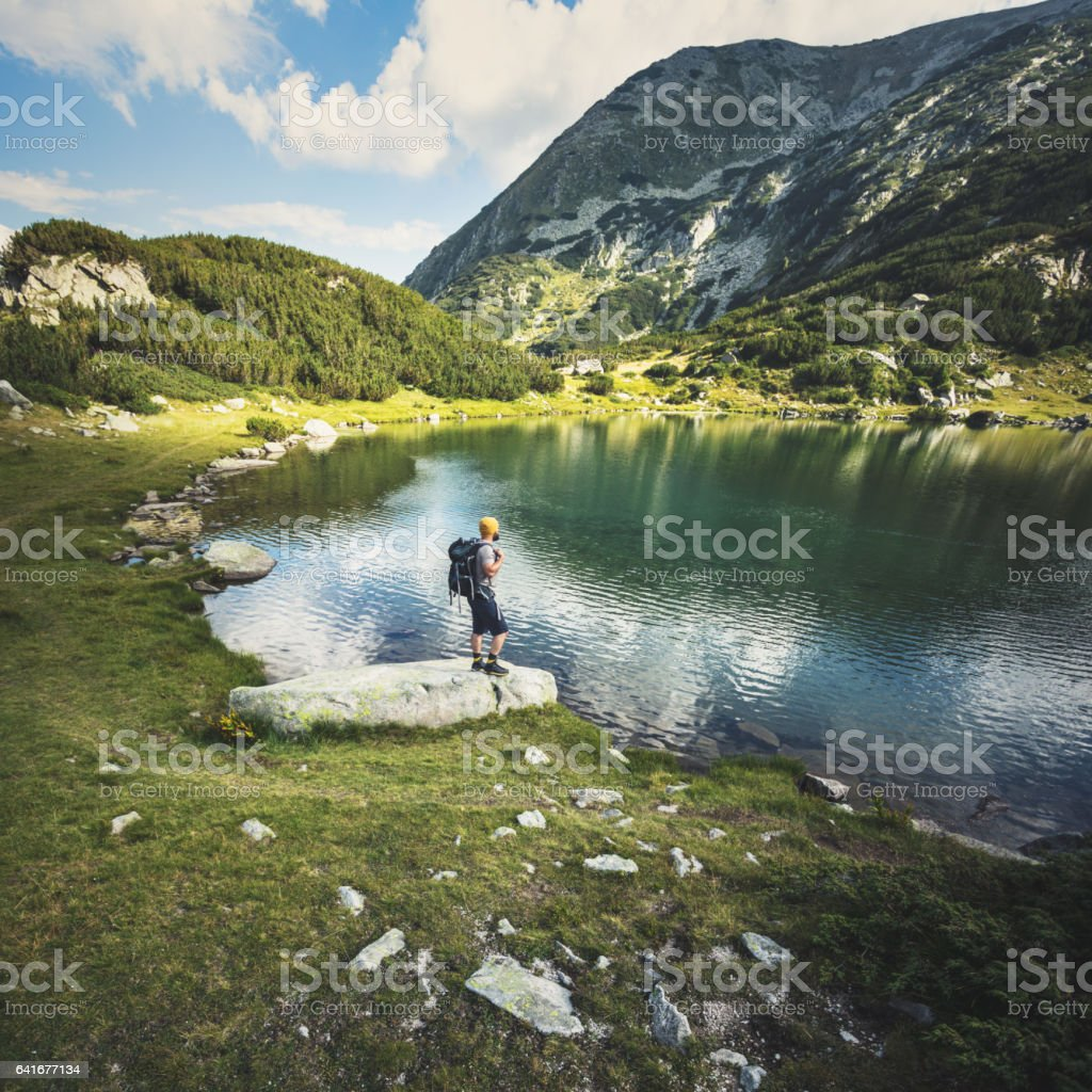 Traveler standing at the lake in mountains stock photo