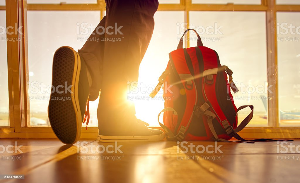 Traveler stands near the backpack at airport. stock photo