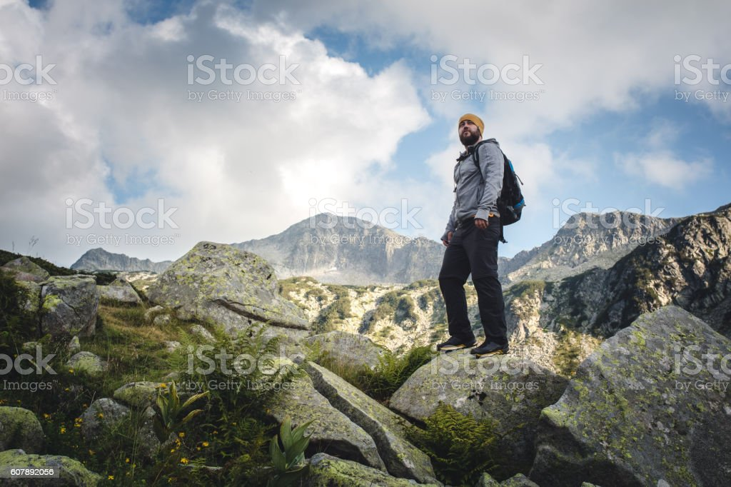 Traveler stands on a huge rocks and looking around. stock photo