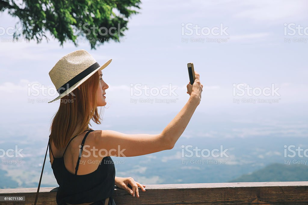 Traveler takes photos on a mobile phone in the mountains. stock photo