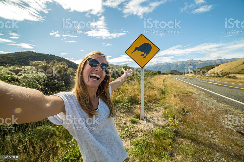 Traveler takes selfie portrait on road with kiwi warning sign stock photo