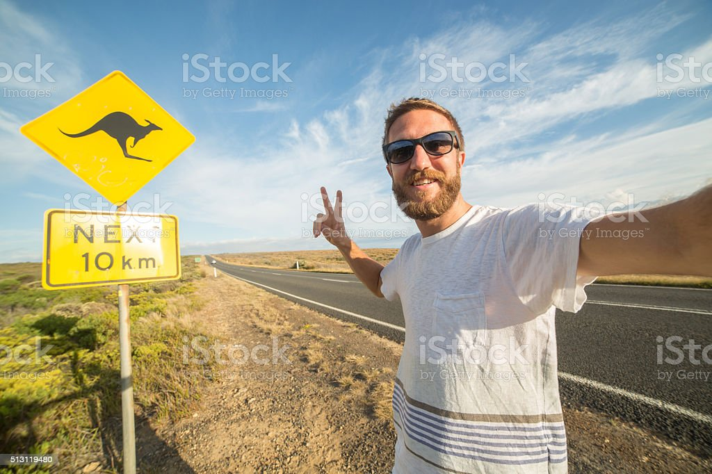 Traveler takes selfie portrait standing next to kangaroo warning sign stock photo