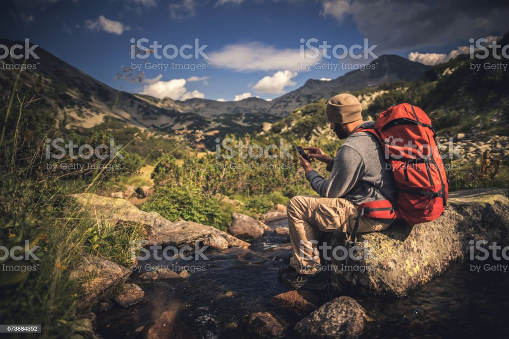 Traveler using a smartphone in the mountains stock photo